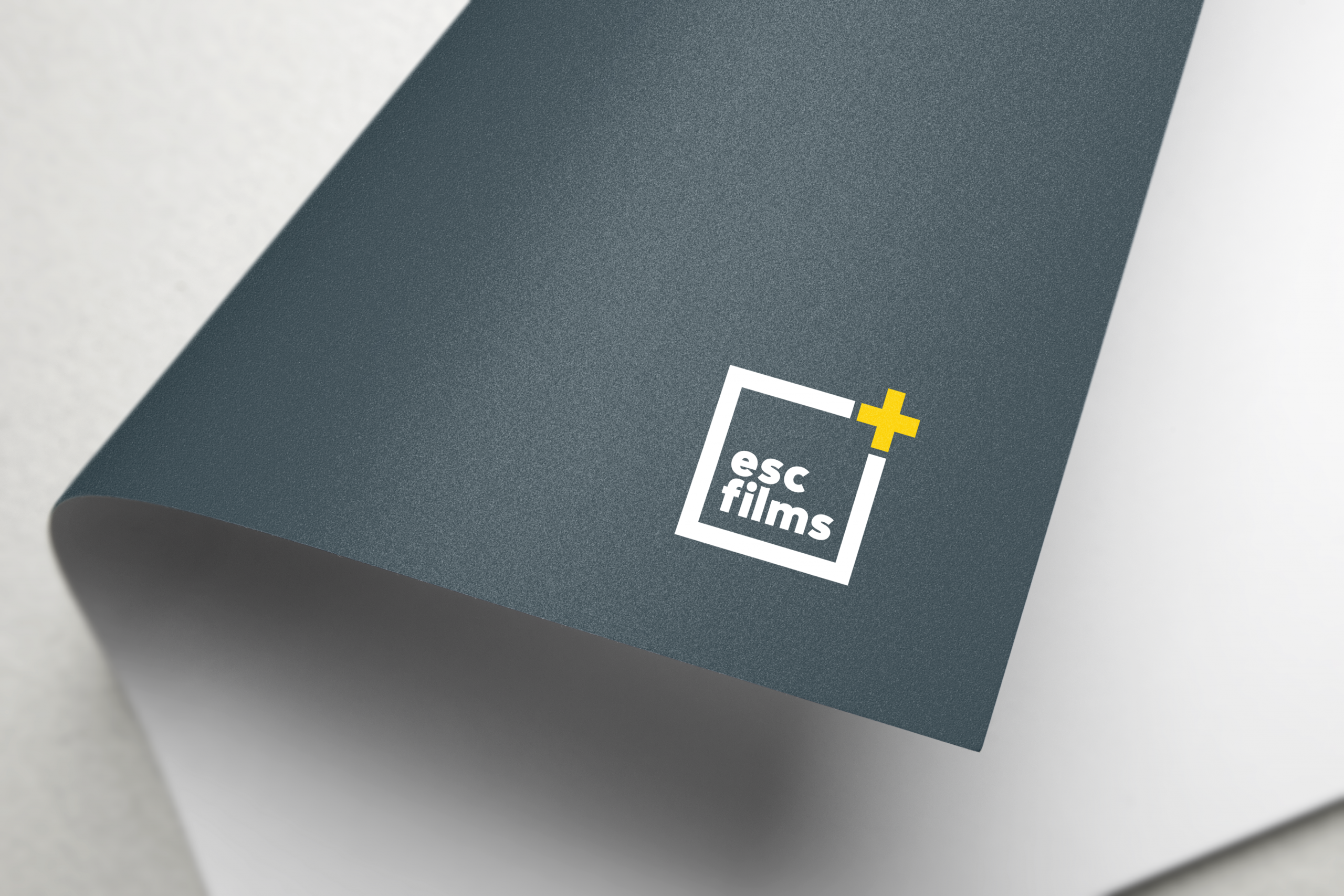 grey rolled up letter with esc films logo in white square with yellow plus sign at top right corner