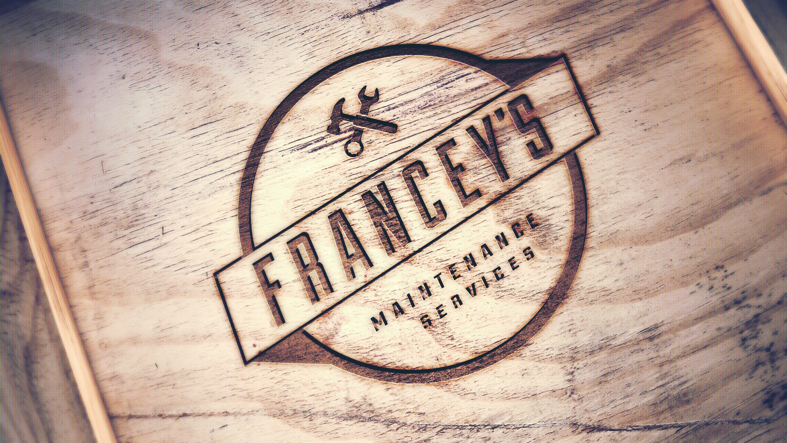 Wood burn of Francey's Maintenance services logo with hammer and spanner