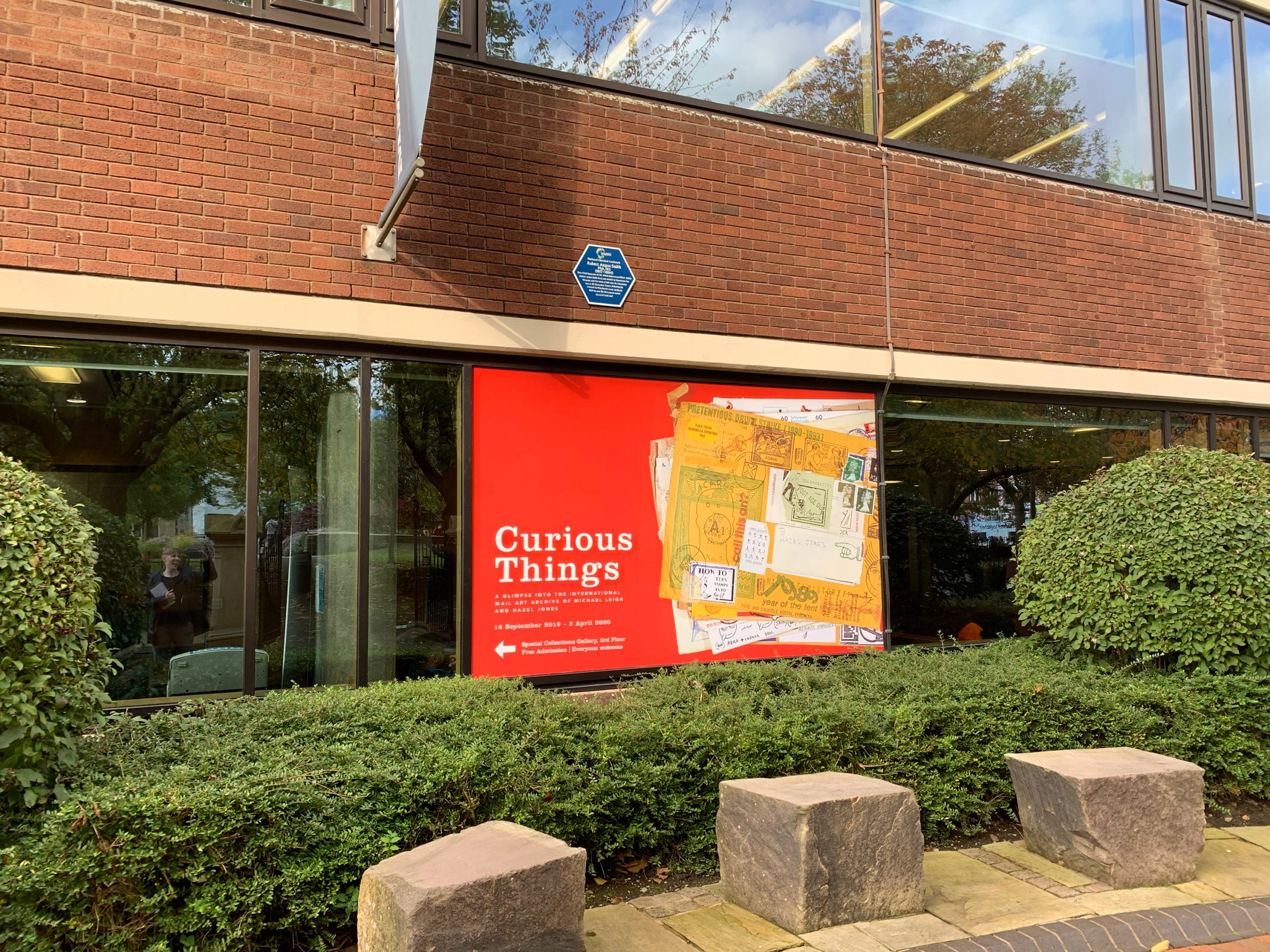 front of library building surrounded by bushes with red window vinyl with stack of mail art envelopes advertising Curious Things exhibition