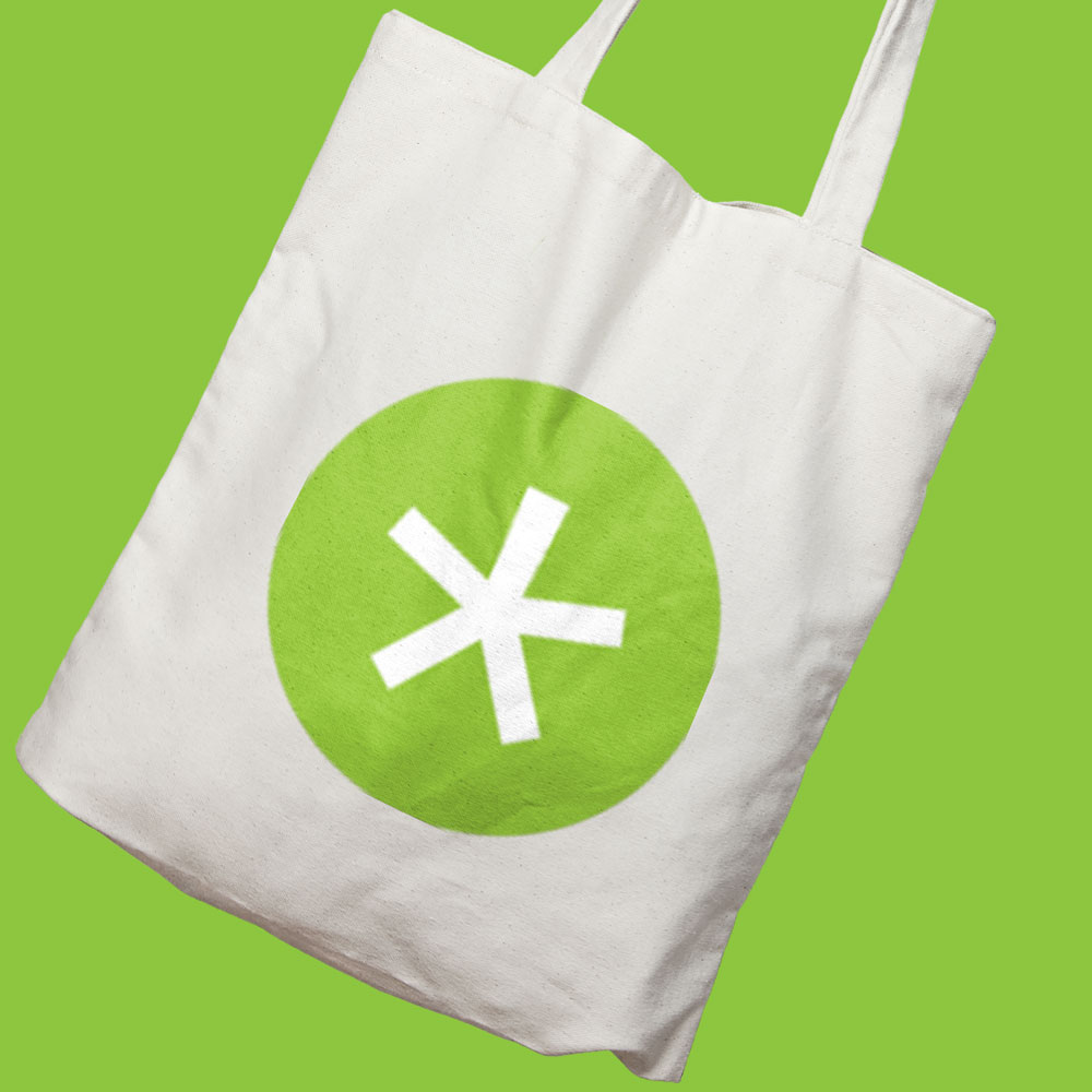 white tote bag with green circle and white asterix, esc productions branded